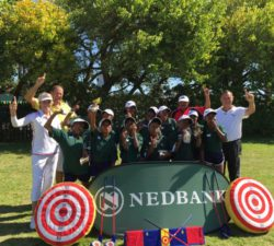 Sally Little and kids and instructors posing in a group behind a Nedbank banner and golf equipment