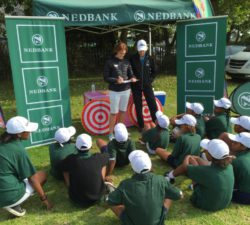 Sally Little and instructor talking to the kids in front of a Nedbank booth