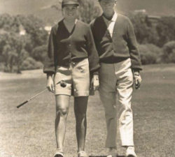 Sally walking on the course next to a man