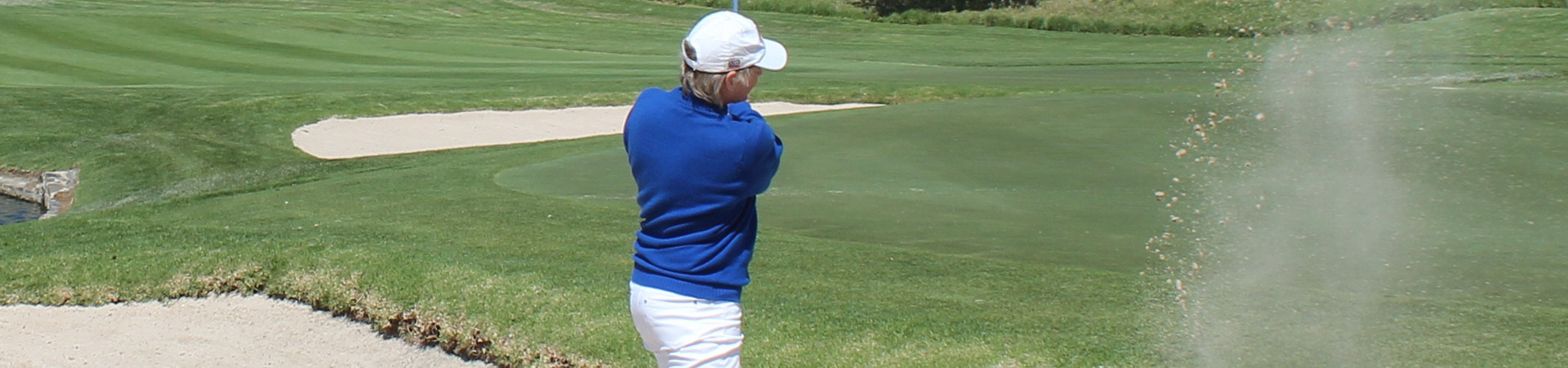 Sally Little hitting a golf ball out of the sand trap
