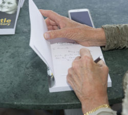 Sally Little personally signing her book to a fan during her book launch for Capturing the Fire