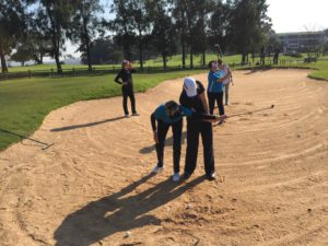 Woman getting assisted trying to get out of the sand trap