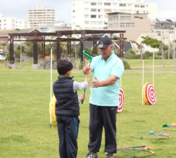 Instructor teaching a kid how to hold the golf club and showing him where his hands should go