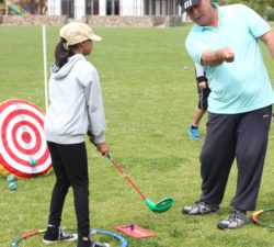 Instructor showing kid where to hit the ball