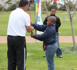 Instructor helping a kid with his golf club handling