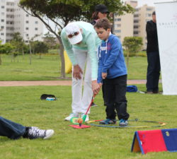 Sally Little helping a kid to aim for the ball when he swings