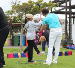 Instructor helping a student with her golf stance