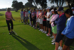 Instructor talking to women standing while holding a golf club