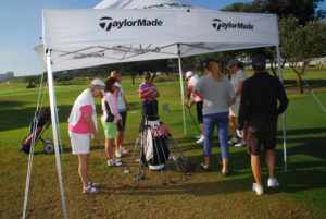 People standing under a white TaylorMade gazebo