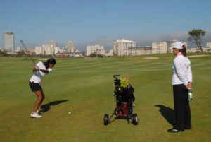 Woman swinging club while being observed by an instructor