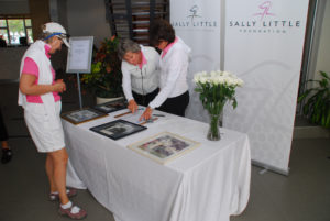 Sally Little and instructors standing by the table for the Sally Little Foundation