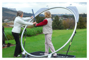 Woman getting a swing lesson from an instructor