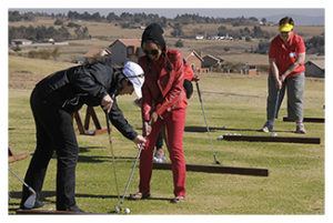 Instructor helping women with her golf club stance