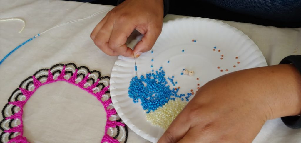 Close up of beaders hands picking up beads with a needle